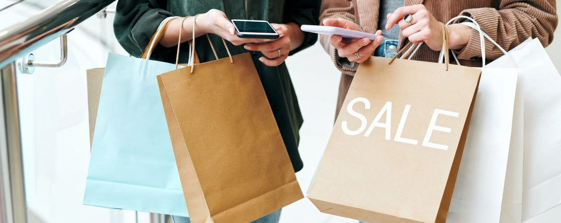 hands-of-two-young-contemporary-shoppers-with-smartphones-and-paperbags-scrolling-through-online-goods-and-comparing-prices